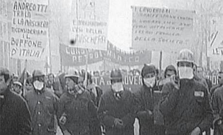 schwarz-weiss-foto mit einander untergehakten arbeitern. mit helmen und atemschutztüchern. viele transparente.